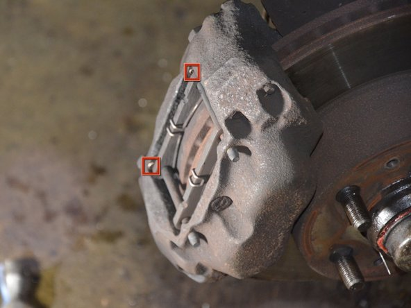Metal clips (shown in red) hold a pair of dowels in place, which in turn hold the brake pads inside the caliper.