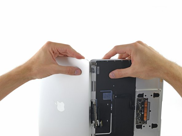 Holding the display assembly with one hand and the upper case with the other, push them together slightly to move the hinges out of their recesses in the the upper case.