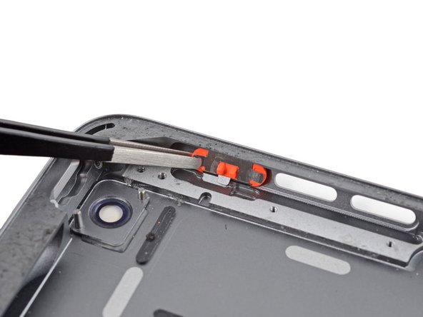 Use a set of tweezers to remove the rotation lock/mute switch from the rear case.