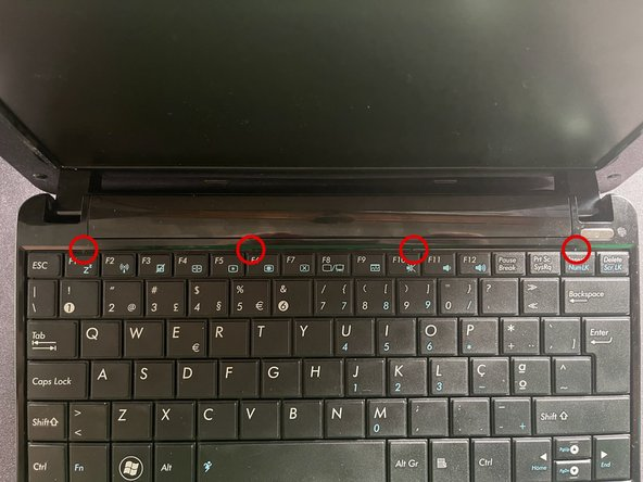 Turn the laptop upside up and open the lid. You should see 4 small pins located next to the top of the keyboard.