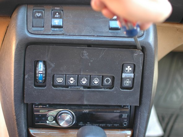 The climate control wood trim is very easy to replace. Use a pry tool to get behind it at the top edge and gently pry it forward.