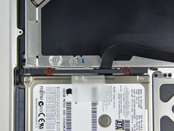 Remove two Phillips screws securing the hard drive bracket to the upper case.
