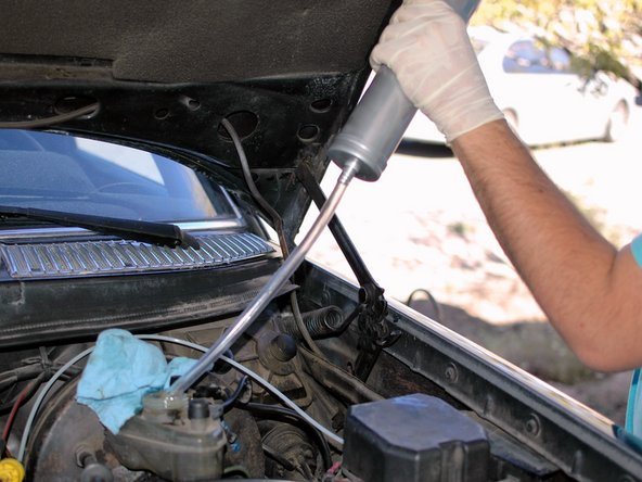 Once you've finished bleeding, remove the power bleeder, being careful not to let the hose drip on your car's paint.
