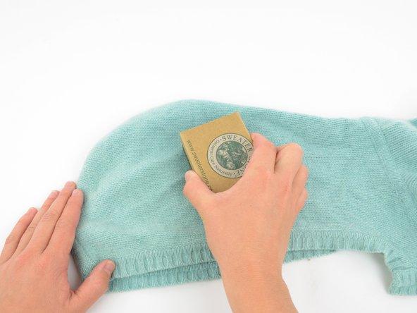セーターの編み目に沿ってセーターストーンでやさしくブラッシングします。