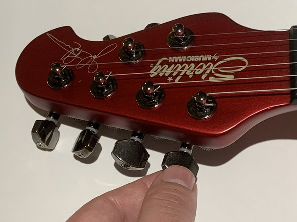 Tune your strings to your desired pitch by playing a note on an open string (not pressing down on any frets) and adjusting the tuning pegs.