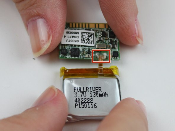Turn the battery and motherboard to the opposite side to expose where they are connected.