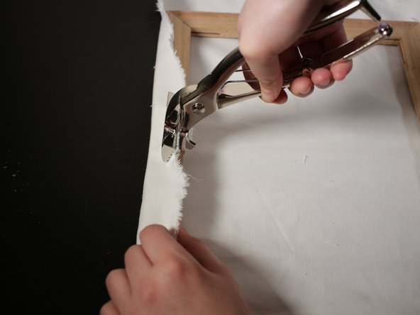 Go over to the other side of the frame and use the canvas pliers to grab the canvas fabric. To tighten canvas fabric, begin by holding the pliers at a 45 degree angle then moving the pliers down towards the table.