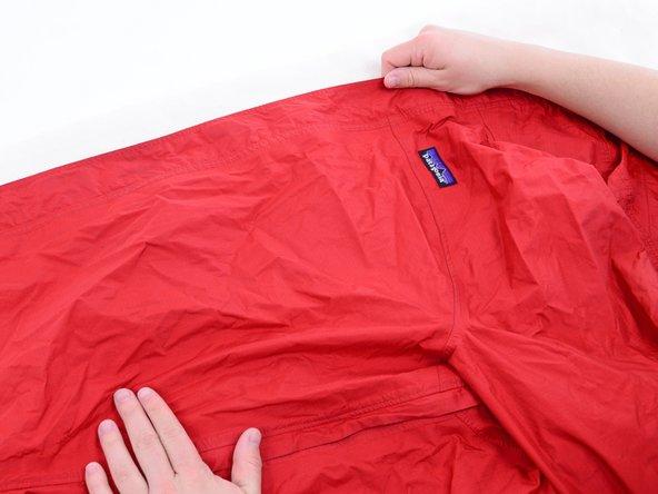 Apri la cerniera della tua giacca già pulita e stendi una delle due metà della giacca sull'asse da stiro.