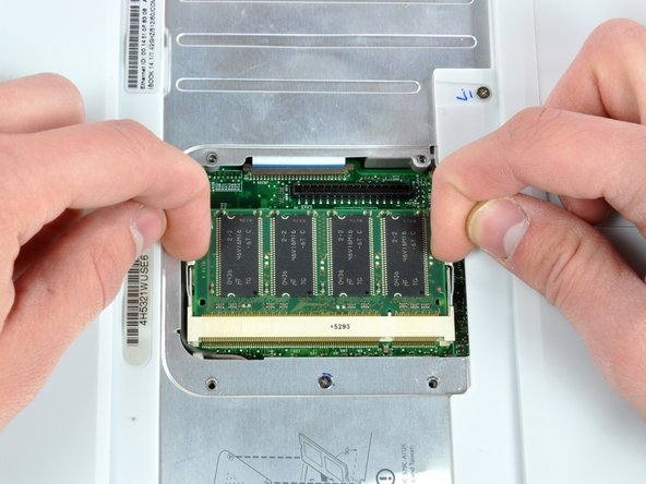 """Release the tabs on each side of the RAM chip at the same time.  These tabs lock the chip in place and releasing them will cause the chip to """"pop"""" up."""