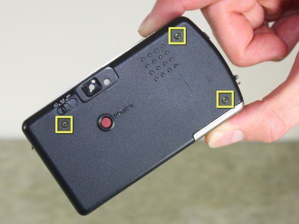 Locate and remove three black 3.80mm screws on the back of the camera with the Phillips #00 screwdriver.