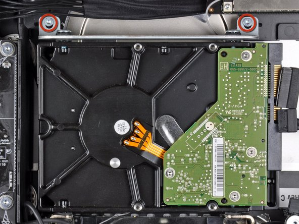 Remove the two T10 Torx screws securing the upper hard drive bracket to the outer case.
