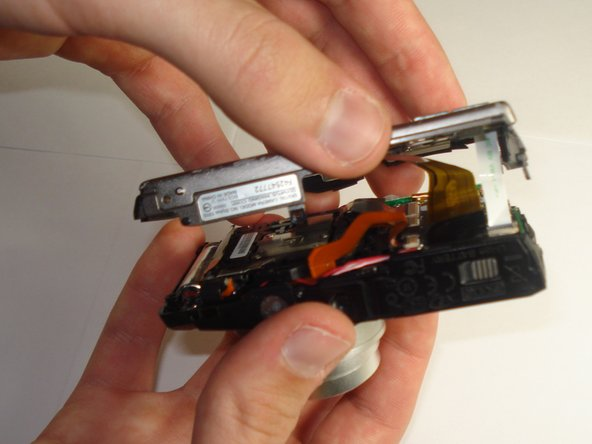 Using a plastic spudger, lift up the black clips.