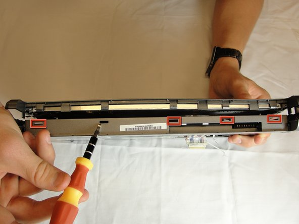 Using a spudger, press in the five tabs on the side where the battery was.