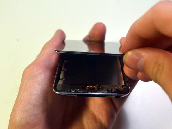 Lift the front panel away from the body of the Touch to peel up the adhesive along its left and right edges.