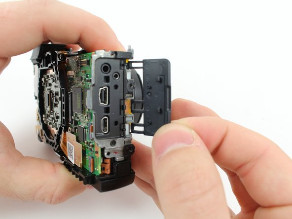 Remove the rubber dust cover from the camera by moving the hooks away from the three prongs holding them in place and then pulling the cover away from the camera.