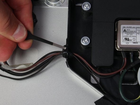 Next, remove the piece of electrical tape that is holding wires into the casing connecting to the power adapter.