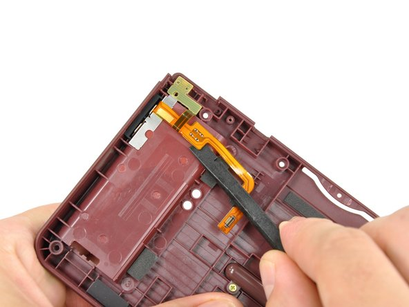 Using the flat end of a spudger, remove the adhesive securing the volume control switch ribbon cable to the back of the battery compartment.