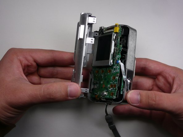 Remove outer case.  Pull the back away from the main body of the camera.