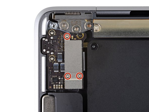 Use a T3 Torx driver to remove the three 1.4mm screws securing the audio board connector cover.