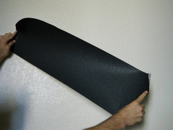 Center the sheet of grip tape evenly over the top of the skateboard deck.