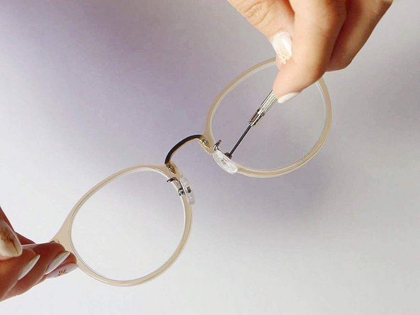 Holding the glasses with the screw head pointing up, tighten the screw  with the screwdriver.