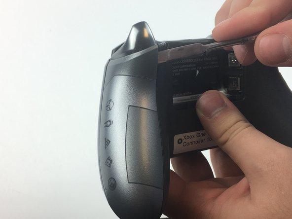 Enlevez les poignées de la manette en glissant une spatule (spudger) dans la fente entre la coque avant et les poignées.