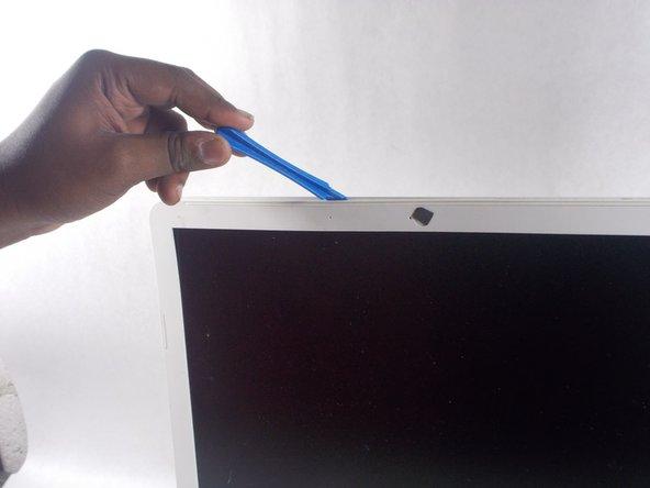 Caler l'outil d'ouverture en plastique à l'arrière du capot de l'écran et le long du périmètre de celui-ci.