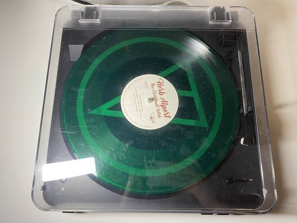 Open the top plastic cover and remove the record and rubber mat.