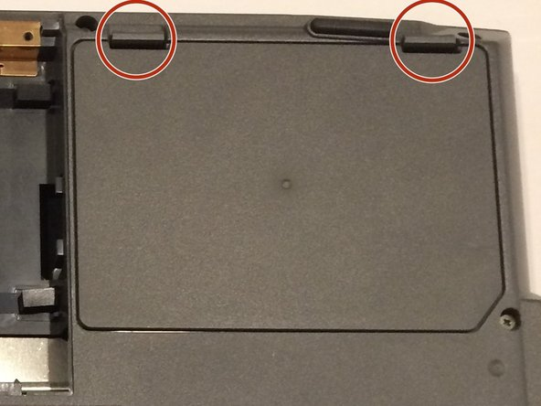 Place your fingers under the two clips, and lift them up simultaneously, pulling the cover towards you to remove the battery.