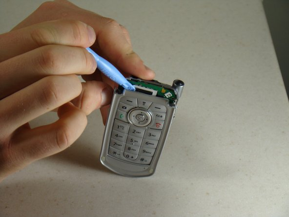 Using the blue pry tool, carefully pull the keypad frame away from the keypad.