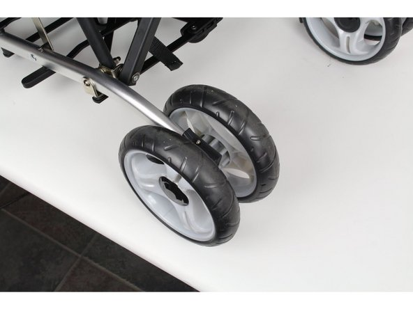 Set the stroller up so the front wheel is on the ground with the metal push tab up.