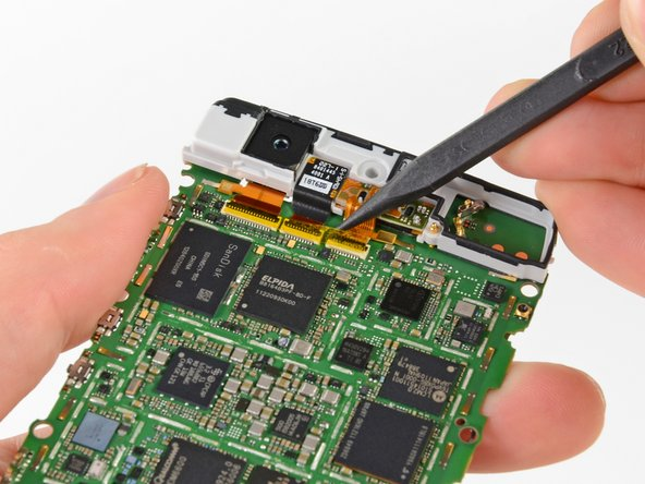 Lift up the anti-static tape covering the camera and earpiece ZIF connectors with the tip of a spudger.