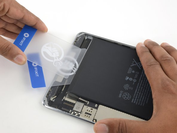 Insert a second plastic card between the battery and first card, this time with the card edge parallel to the battery.