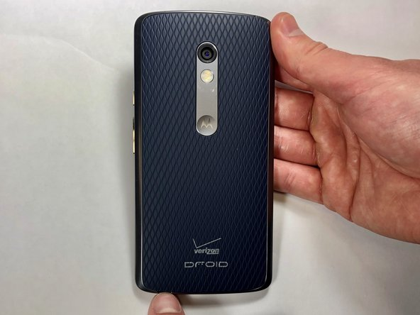 Wedge your thumb into the indent located on the bottom left corner of the back cover and pull up to remove the back cover.