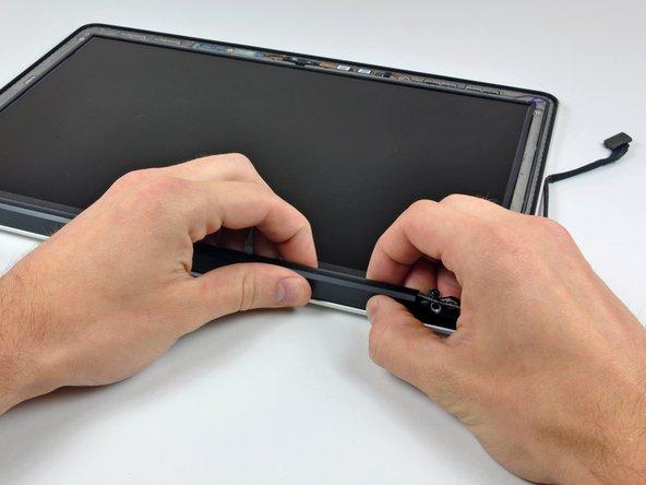 Beginne ganz rechts und rüttle die Verschlussabdeckung vorsichtig auf ihrer langen Achse vor und zurück und ziehe sie dabei vom Display weg.