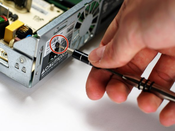 Remove the 140 mm T8 screw from the back of the TiVo premiere XL4 box holding the power supply in place using a Torx screwdriver.