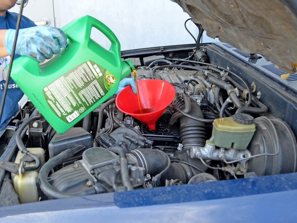 Pour 5 quarts of 10W-30 automobile oil into the engine. Use one hand to stabilize the funnel to help prevent spills.