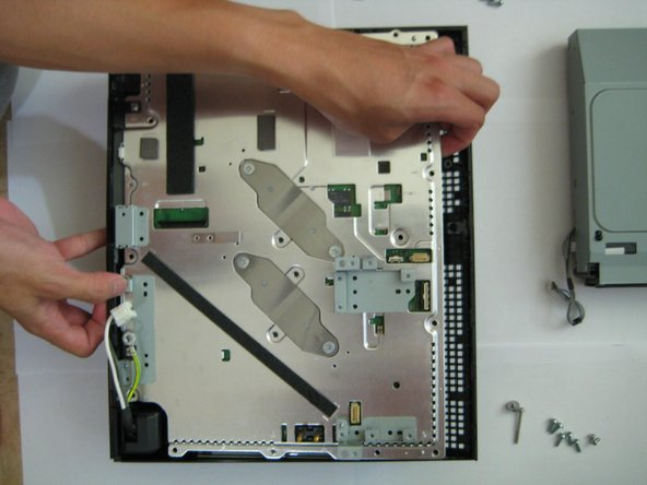 Grab the main board at the locations shown in the picture and lift the main board off of the back casing.