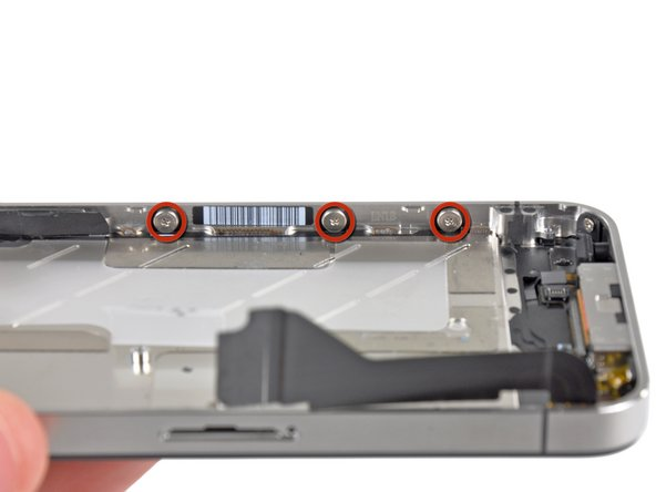 Remove the three large-headed 1.5 mm Phillips screws along the volume button side of the iPhone.