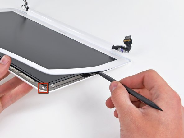 Use your spudger to pry the left side of the front display bezel away from the display assembly.