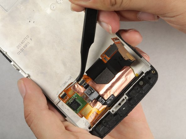 Lift the digitizer wiring with a pair of tweezers but do not pull out the wiring.
