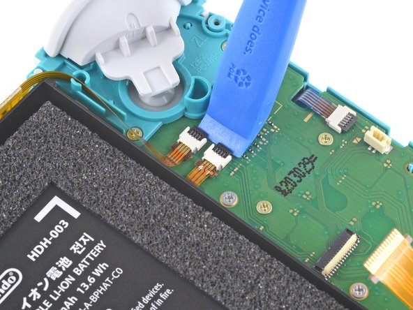 Use an opening tool or your fingernail to flip up the small, hinged locking flaps on the two ribbon cable ZIF connectors.
