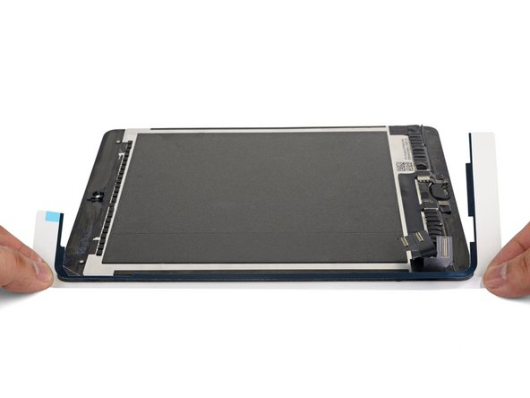 Align the left adhesive strip to the left edge of the display assembly.