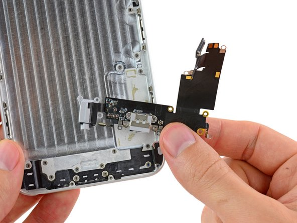 Lift and remove the Lightning connector and headphone jack cable assembly out of the iPhone.