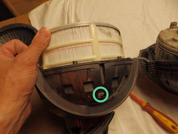 Der Obere Teil ist durch 2 Rastnasen am Gehäuse eingeklipst.  Mit einem Schraubenzieher und etwas Hin- und Herbewegen von Hand lassen sie sich aushängen. Packe nicht zu fest an dem HEPA Filter an, da er aus Papier besteht und leicht eingedrückt wird.