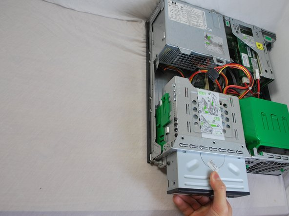 Grasp the optical drive with your right or left hand and pull the drive out towards you.