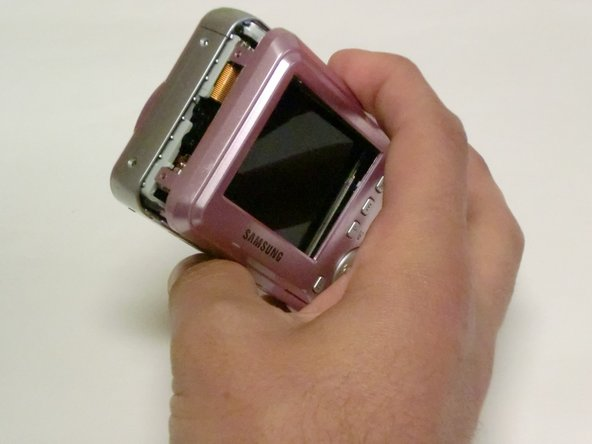 Carefully pull the back case (the side showing the  LCD screen) away from the front half.