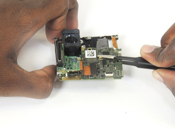 Using tweezers, lift the motherboard from the midframe housing