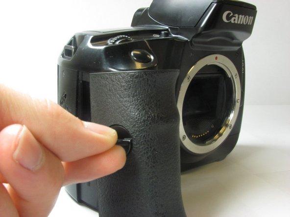 Tournez la languette dans le sens des aiguilles d'une montre pour déverrouiller la porte, puis tirez vers l'extérieur de la caméra pour la retirer.