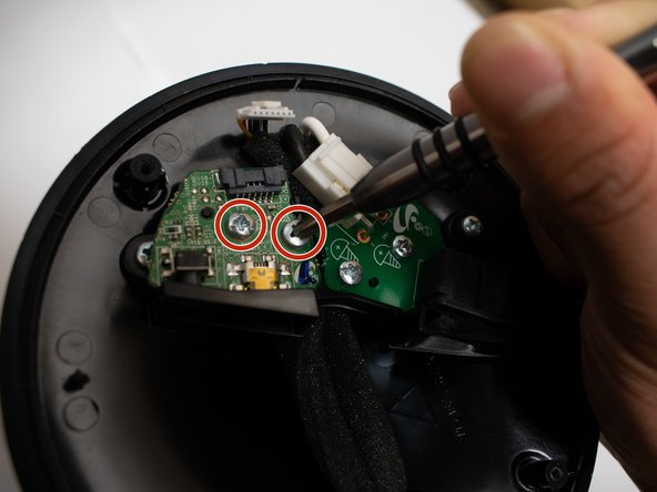 Remove the two 10mm long screws from the board utilizing the Phillips #1 screwdriver.